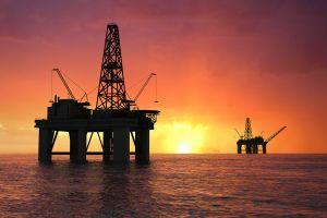 Oil rig silhouette over orange sky