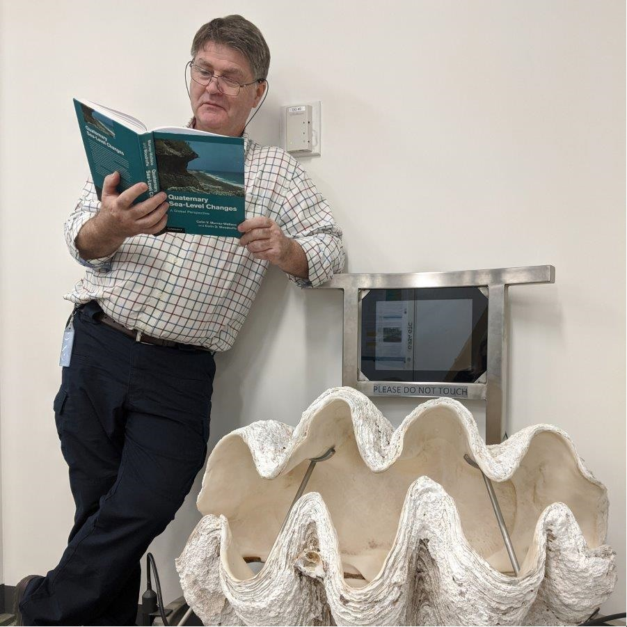 The reviewer reading the book while standing next to the shell of a giant clam