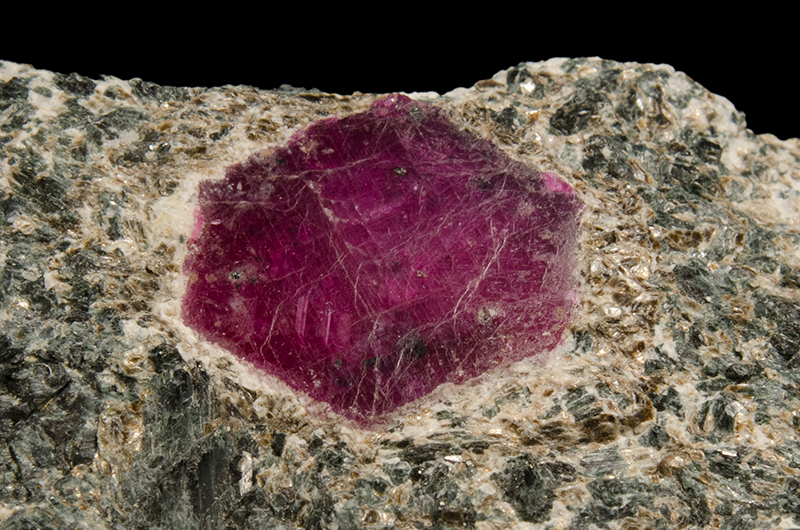 A magenta coloured hexagonal shaped ruby crystal in a grey and white rock