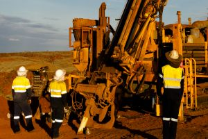Three employees operating an exploration drill rig in the outback Pilbara region of Australia.
